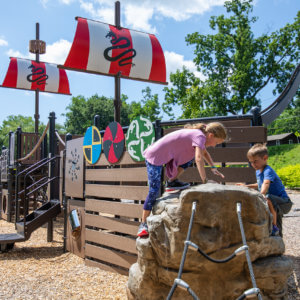 Photo of a ship inspired play structure with a boulder shaped climber, sails, and a slide