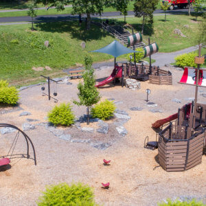 Panoramic view of the playground's different play areas, surrounded by trees and grass