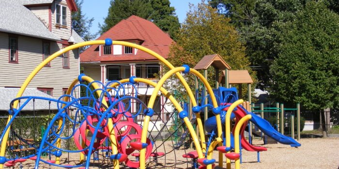 Photo of curved play structure with climbing nets, ladders, and slides.