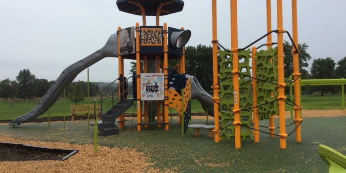Photo of playground with two multi-level towers, one with a climbing structure and the other with multiple slides and play panels.