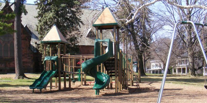 Photo of playground with slides, climbers, and peaked roofs.