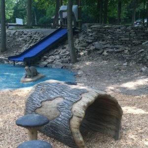 Photo of log shaped tunnel and mushroom steppers, with hill slide and concrete otter in the background.