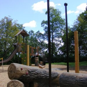 Photo of log shaped seats and a tall playstructure with climbers and a slide.