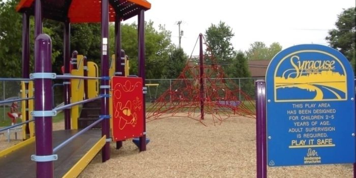 Photo of playground with spinners, net climbing structure, and decks with accessible ramp.