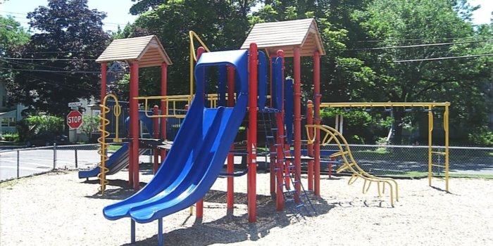 Photo of playground with slides, climbers, and bridge.