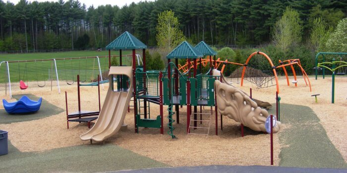 Photo of playground with slides, climbers, swings, and independent spinners.