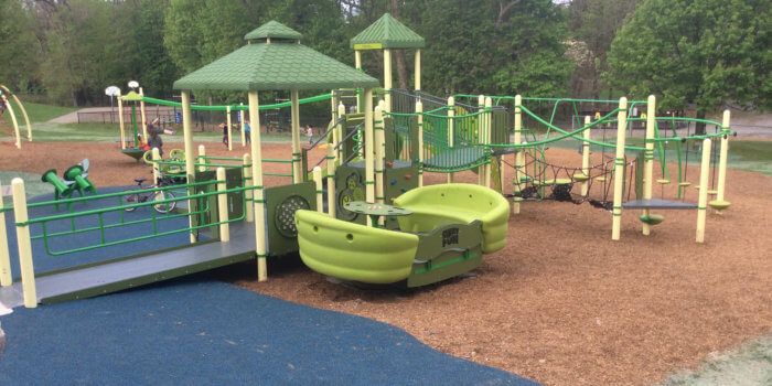 Photo of playground, including multiple play structures and a wheelchair accessible glider