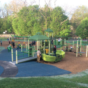 Photo of the overall playground with multiple play structures and a wheelchair accessible glider