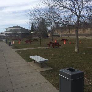 Photo of the site prior to playground installation - grassy area with a few trees and picnic tables scattered throughout.