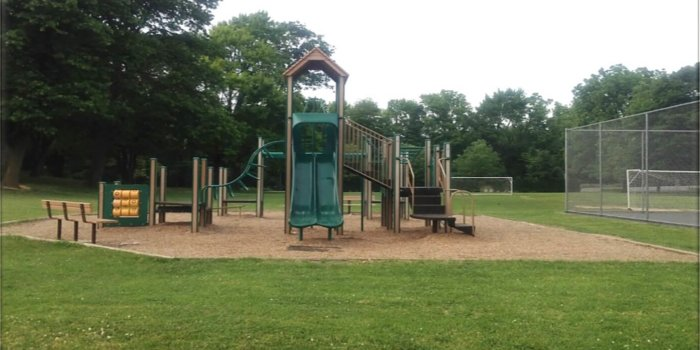 Photo of a playground with slides, climbers, and play panels.