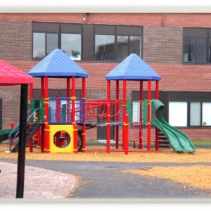 Photo of playground with slides, climbers, and play panels.