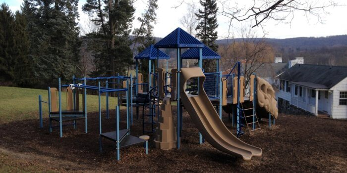 Photo of playground with slides, climbers, and overhead play components.
