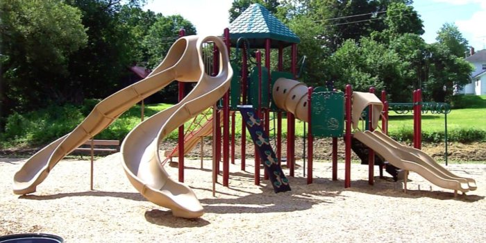 Photo of playground with several slides, climbers, and play panels.