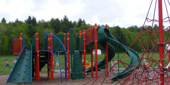 Photo of play structure with slides, climbers, and a curved net climbing structure.