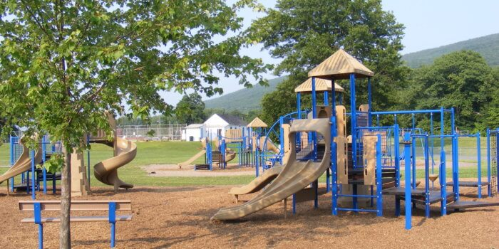 Photo of playground with mutiple structures, each with slides, climbers, and roofs.