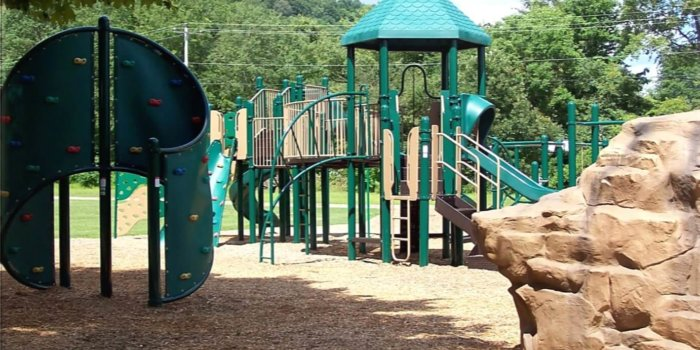 Photo of playground with climbing wall structure, slides, decks, and climbers.