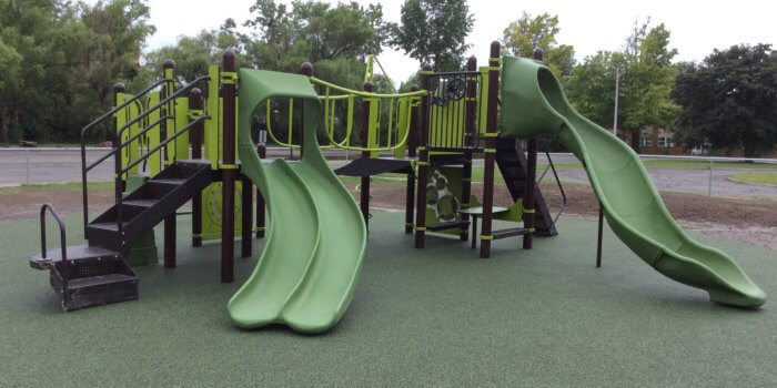 Photo of play structure with slides, climbers, and play panels on poured in place rubber surfacing.