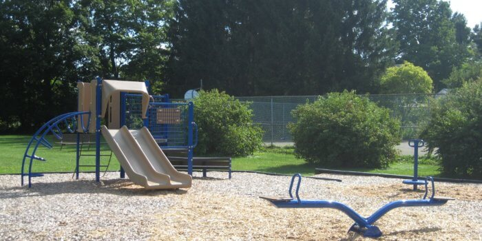 Photo of spinner, seesaw, and play structure with climbers and slides.