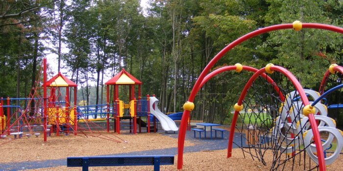 Photo of playground with numerous play structures, including climbing nets, slides, and bridges.