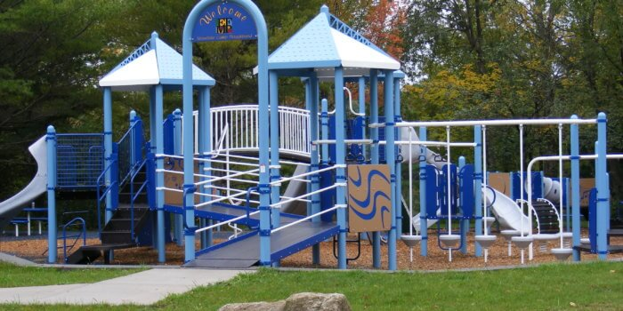 Photo of playground with wheelchair ramps, slides, tunnels, bridges, and climbers.