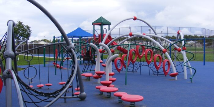 Photo of playground with curved net climbing structures, climbers, and slides.