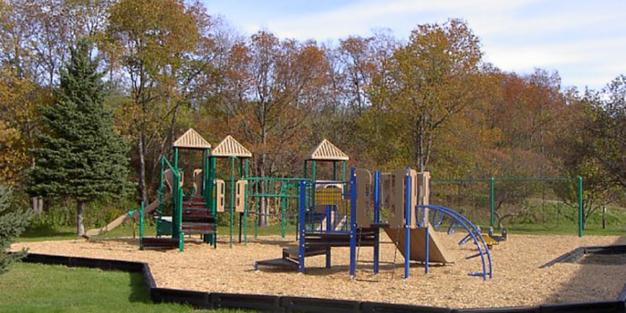 Photo of playground with two play structures, each with decks, climbers, and slides.