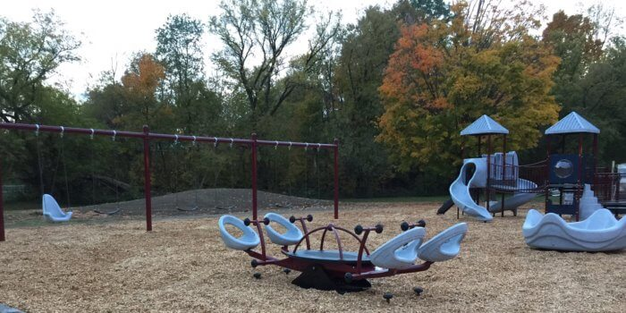 Photo of playground with swings, seesaw, and play structure with swings and climbers.