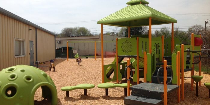 Photo of play structure with play panels, climbers, a slide, and a sensory dome shelter.