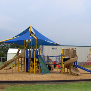 Photo of a large play structure with climbers, multi-level decks, and slides, as well as a large shade overtop