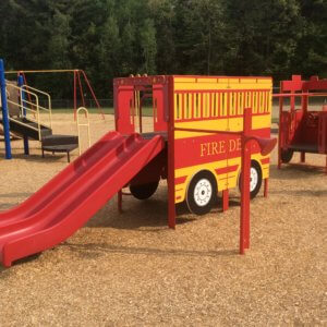 Photo of a fire-truck shaped play structure with slides and climbers