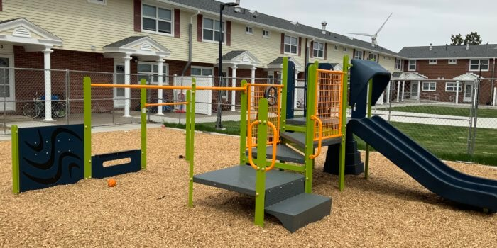 Photo of playground with slide, climbers, and play panels.
