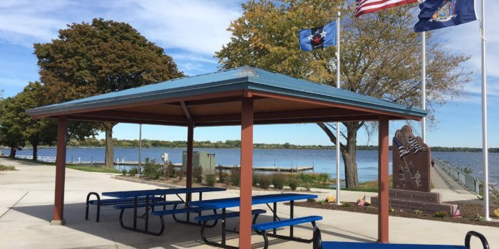 Photo of a large outdoor shelter with benches in front of a lake.