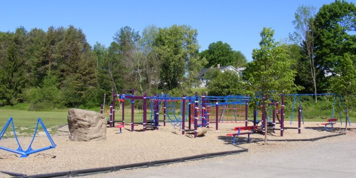 Photo of playground with climbing nets, ladders, swings, and a see saw.