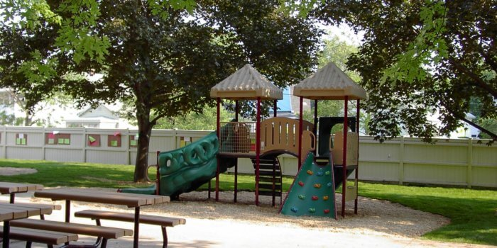 Photo of playground with slides and climbers, and picnic tables.