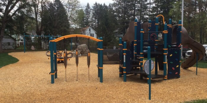 Photo of playground with play structure, seesaw, and swings.
