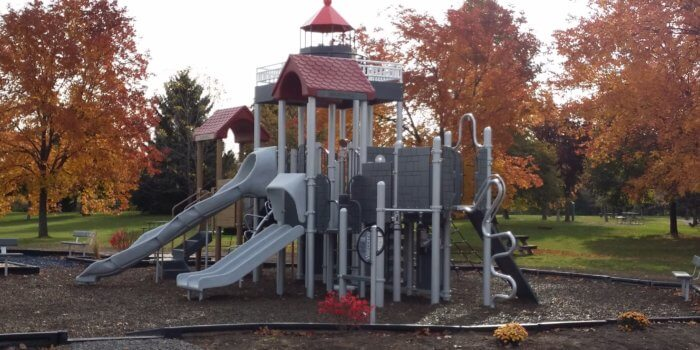Photo of a lighthouse-inspired play structure, with slides, climbers, and multiple levels of decks
