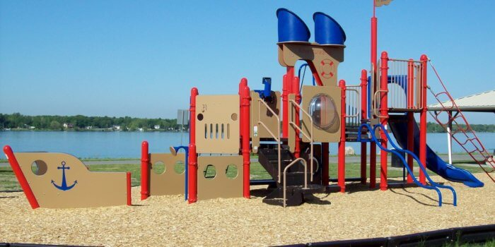 Photo of play structure shaped like a ship, with climbers, panels, a slide, and a flag.