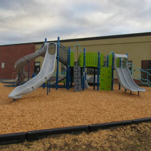 Photo of a play structure with numerous decks, slides, and climbing components