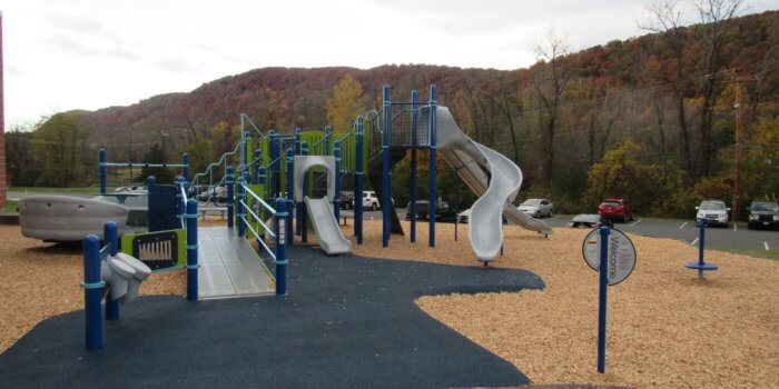 Photo of a ramp leading to a play structure with multiple slides, decks, and an attached glider