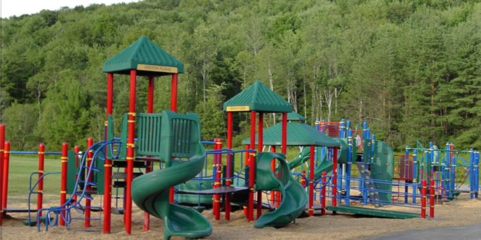 Photo of playground with bridges, slides, climbers, and accessible ramp.
