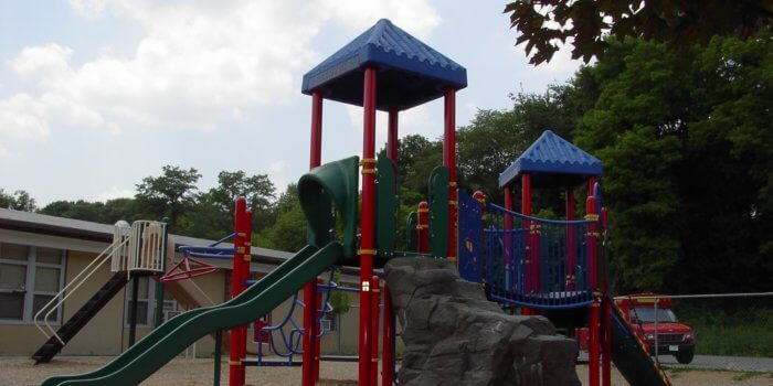 Photo of playground with bridge, slides, and climbers,.