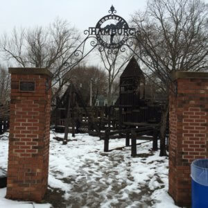 Photo of the old community playground behind the preserved brick and iron archway