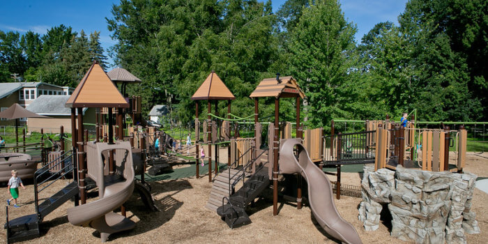 Photo of the overall playground site, showing multiple large play structures with climbers and slides