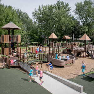 Photo of playground with multilevel play tower and numerous other play structures.