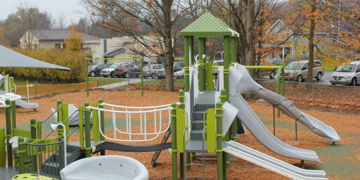 Photo of playground with slides, bridge, and glider.