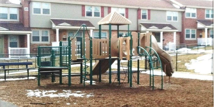 Photo of playground with climbers, slides, and multiple levels of decks.