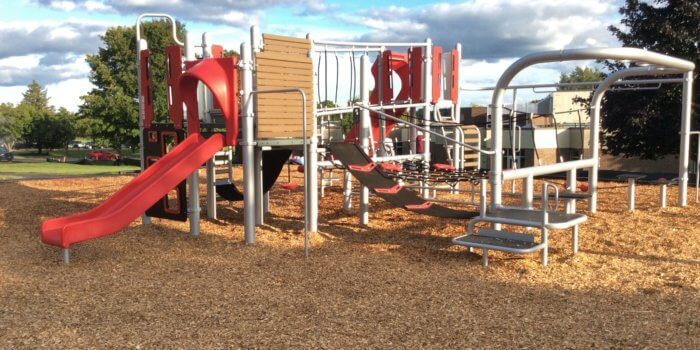 Photo of play structure with multiple geometric climbers, bridges, and slides