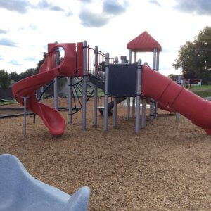Photo of play structure with multiple levels of decks, slides, and climbers