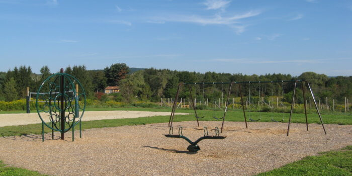 Photo of swings, seesaw, and climbing structure.