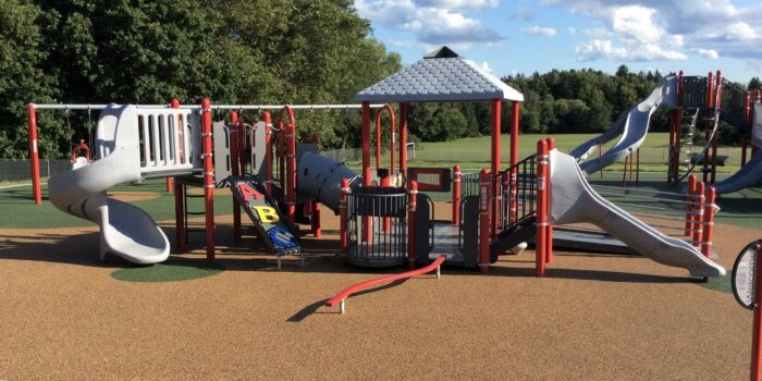 Photo of two large playground structures, each with several climbing components, slides, and decks.